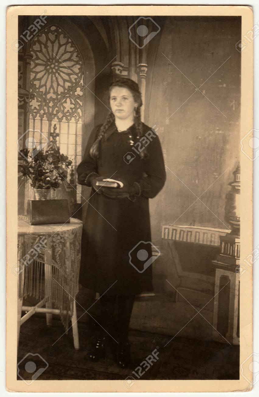 GERMANY - CIRCA 1940s: Vintage photo shows young woman poses with book, she  stands