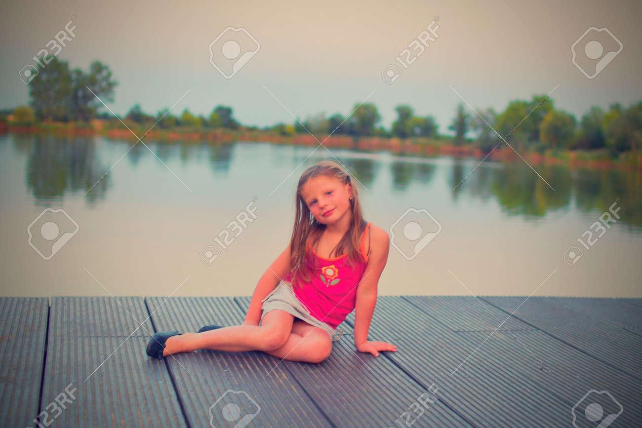 Little girl sitting on pier  Preschool girl sitting on a wooden