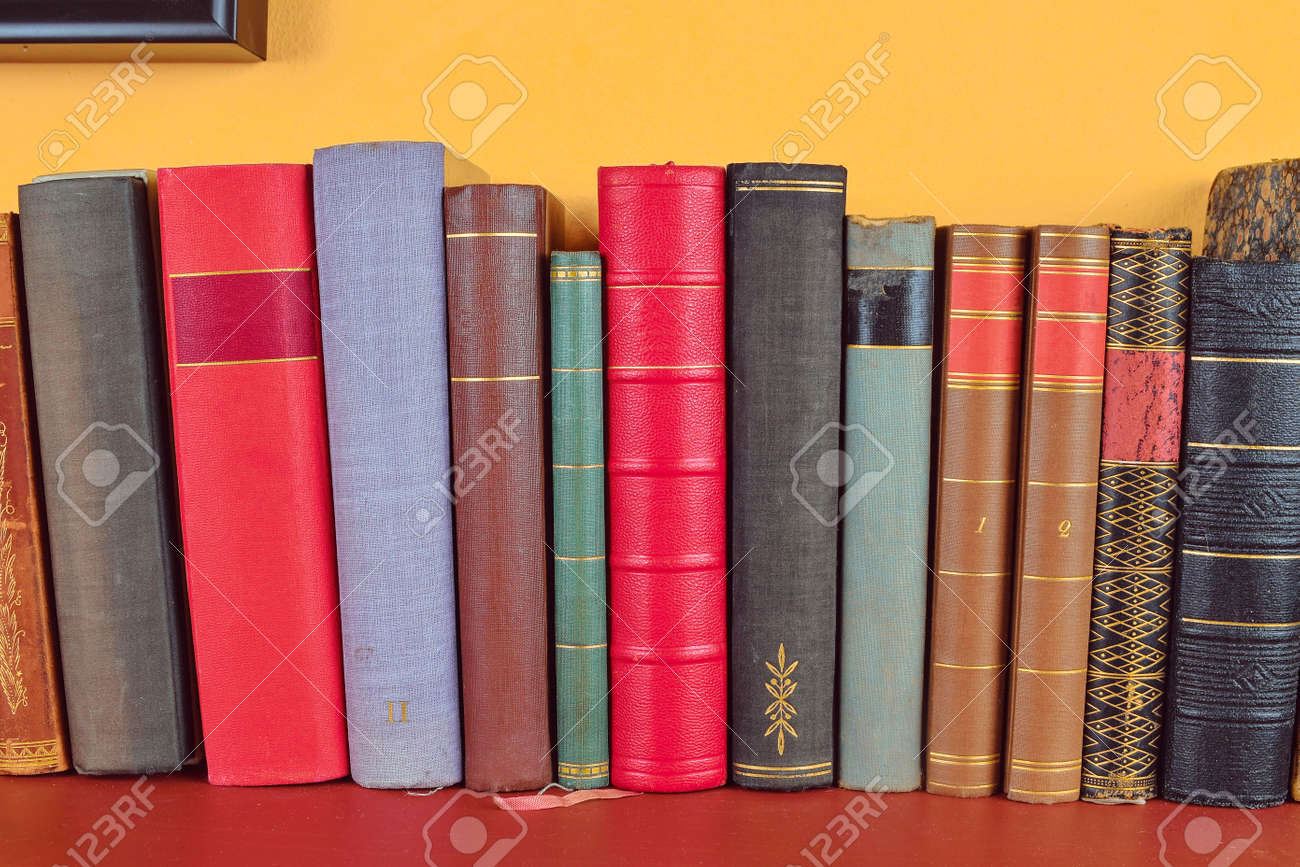 Wooden shelf with historic,decorated, vintage books. Old books on yellow and claret background - 114489466