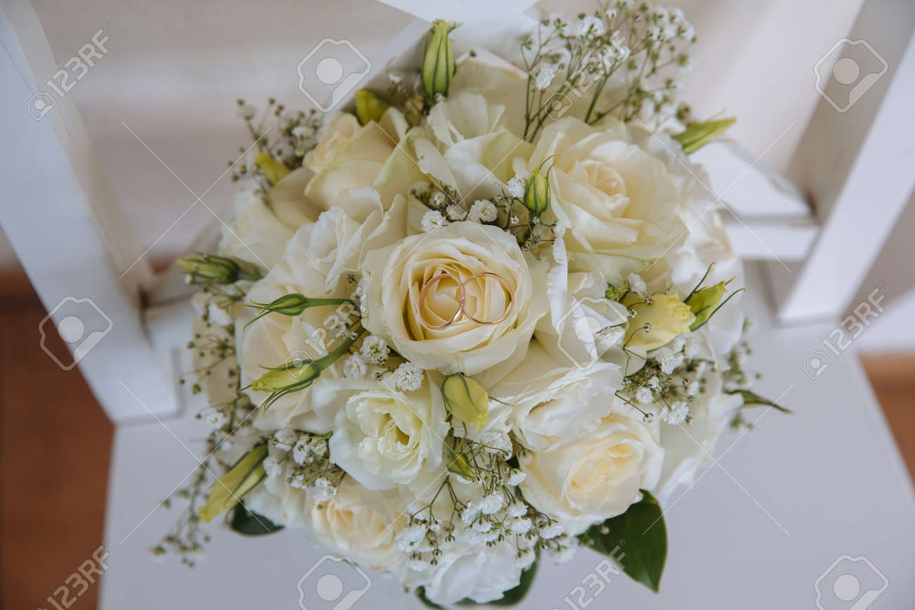Gold Rings On Wedding Bouquet Of Blue And White Fresh Flowers Stock