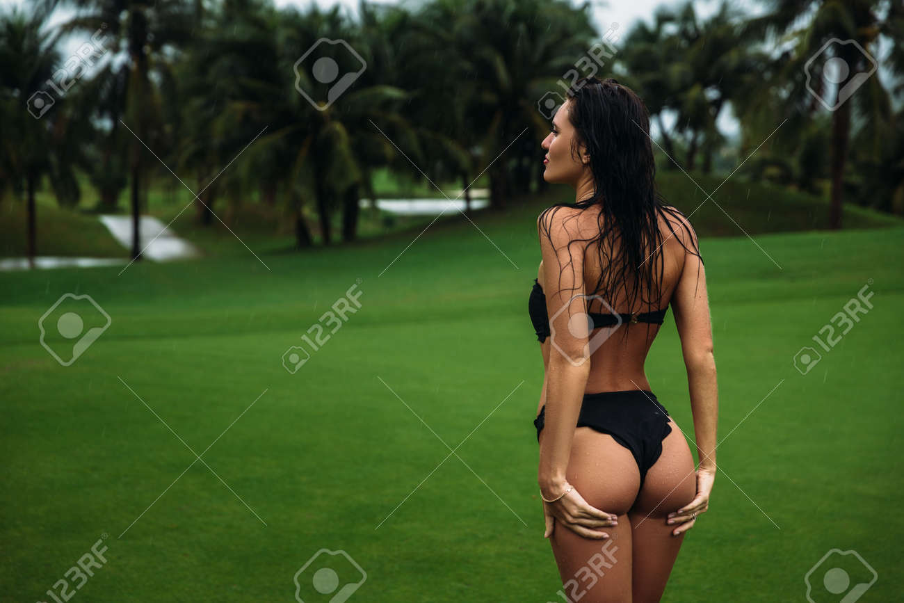 Young sexy and beautiful brunette fitness girl in black swimsuit..