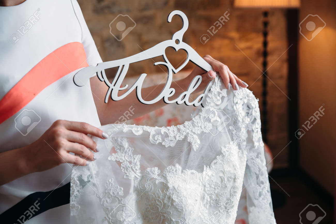 The Bride Is Holding A Dress On A Hanger Stock Photo, Picture And ...