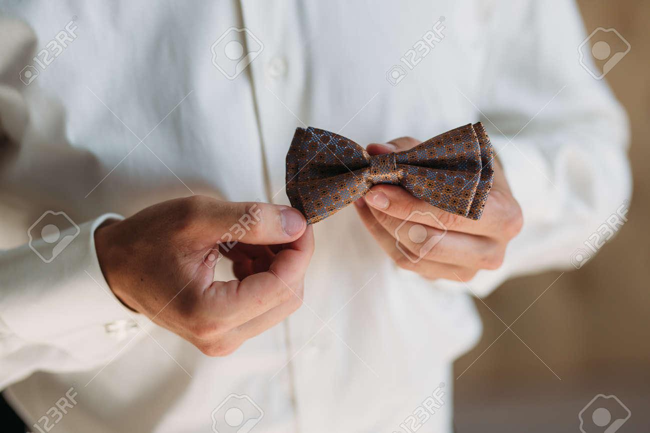 75de28320507 Banque d images - Mains de marié Close-up avec noeud-papillon. Élégant  clother gentleman, chemise blanche et ceinture marron
