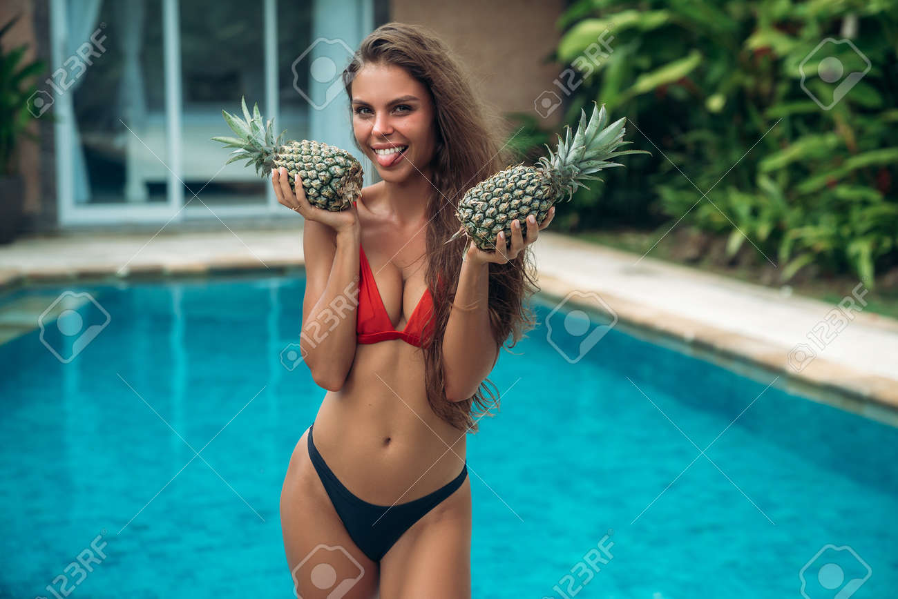 Portrait of young beautiful brunette girl in swimsuit with pineapple in her  hands fruit holding on the breast. Sexy model with cute smile, ...