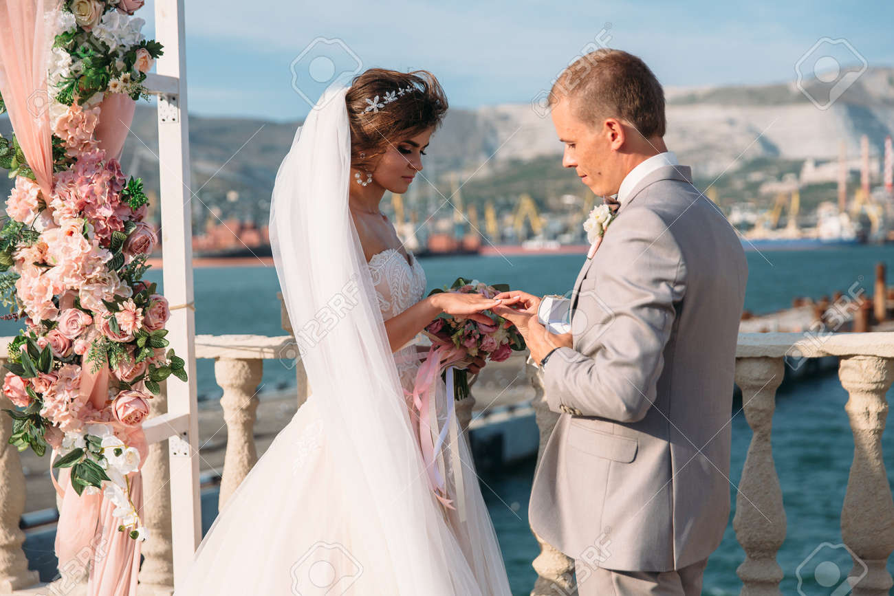 couple in wedding arch exchange rings with lake on background, the bride with long beautiful hairs and groom in black suit look at each other in wedding day. Concept of love and family - 100867807