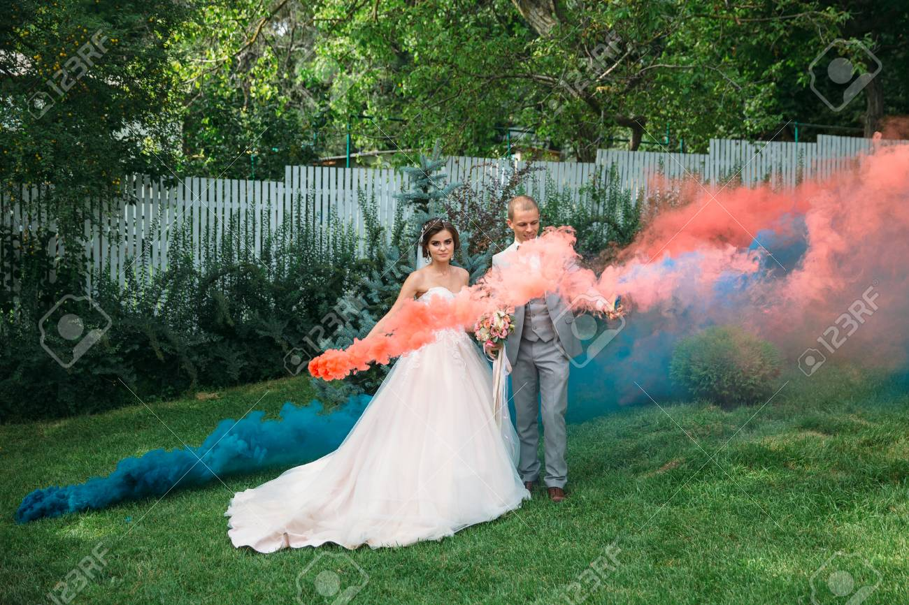 The bride and groom with smoke bombs on a field with green grass