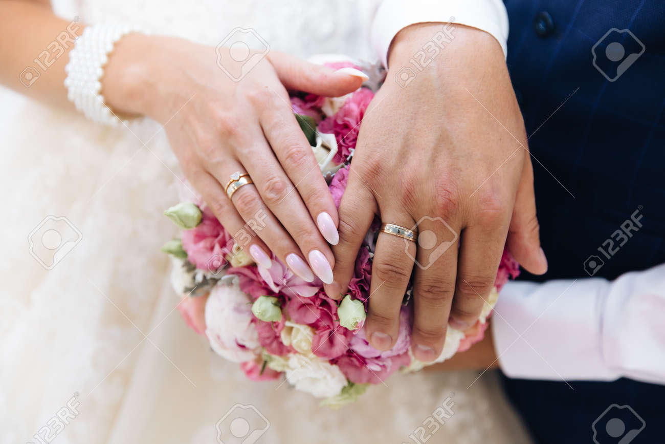 Close-up of the hands of the newlyweds with wedding rings, gently touch the wedding bouquet of peonies. - 110134072