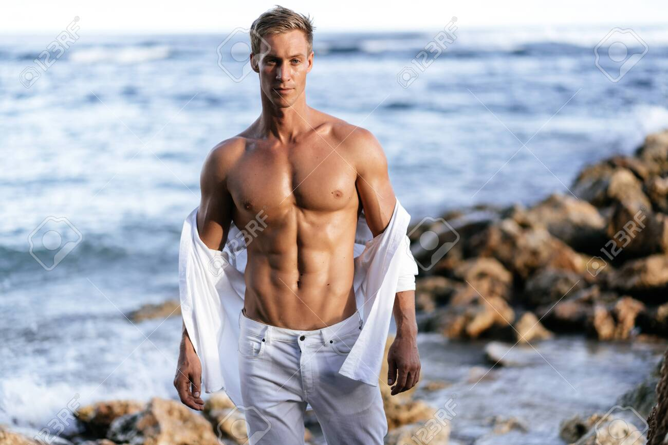 Muscular athletic man in white pants with a torso on the beach. - 124445854