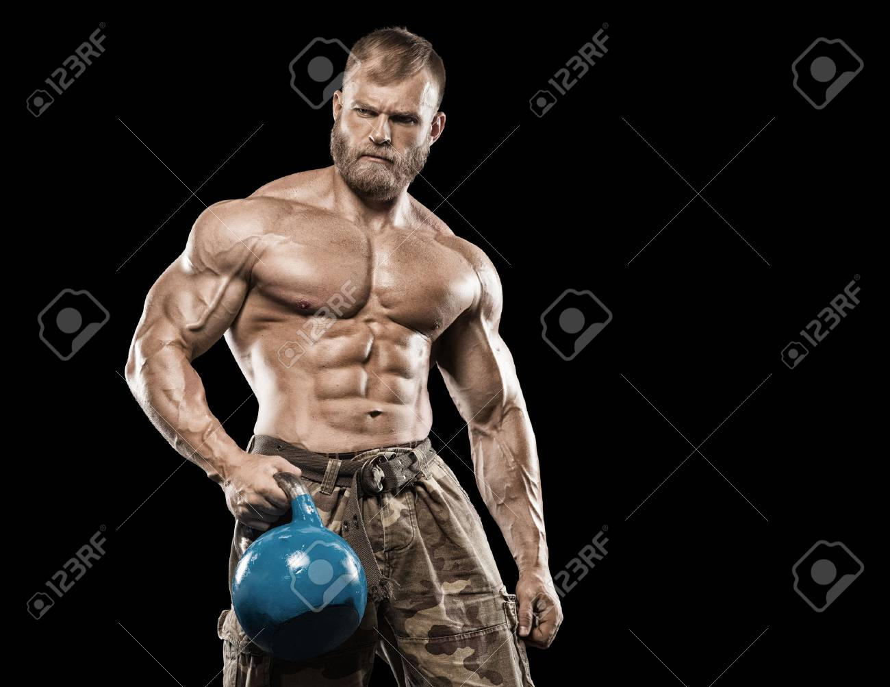Muscular athletic bodybuilder fitness model posing after exercises