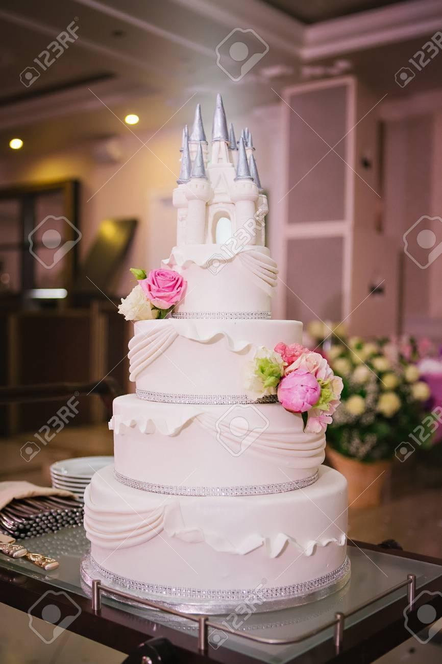 Archivio Fotografico , Torta nuziale a più livelli decorata con fiori e un  castello