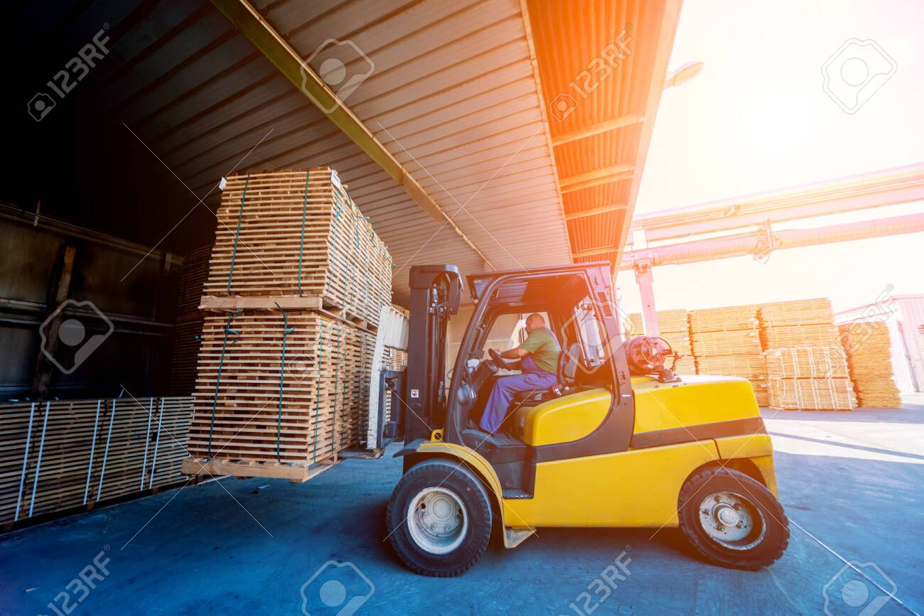 Forklift loader load lumber into a dry kiln. Wood drying in containers. Industrial concept - 139116437