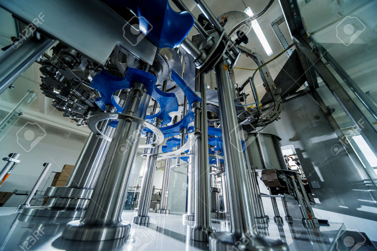 Automatic filling machine pours water into plastic PET bottles. - 139938495