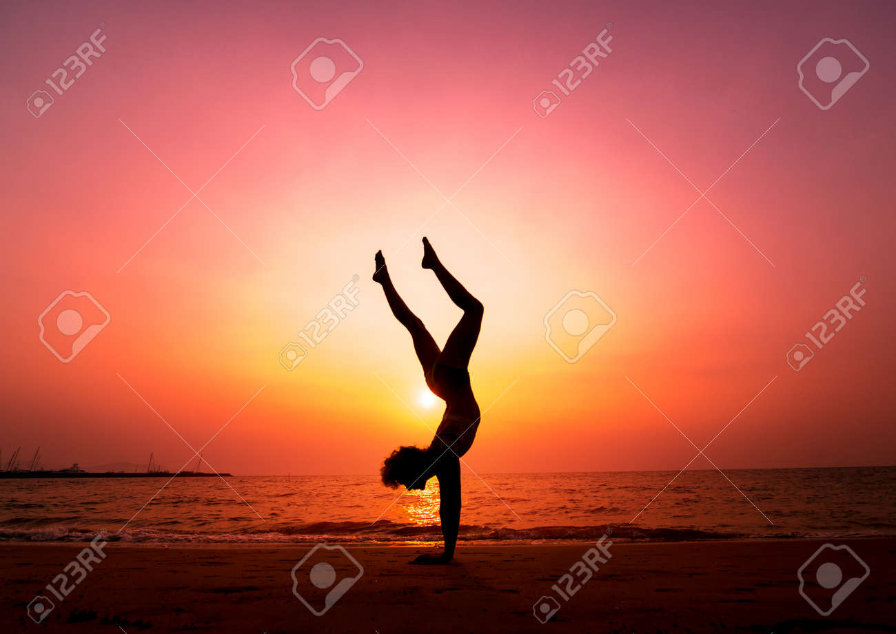 Beautiful young woman practic yoga at the beach. Early morning exercise. Sunrise. Palms background - 140459153