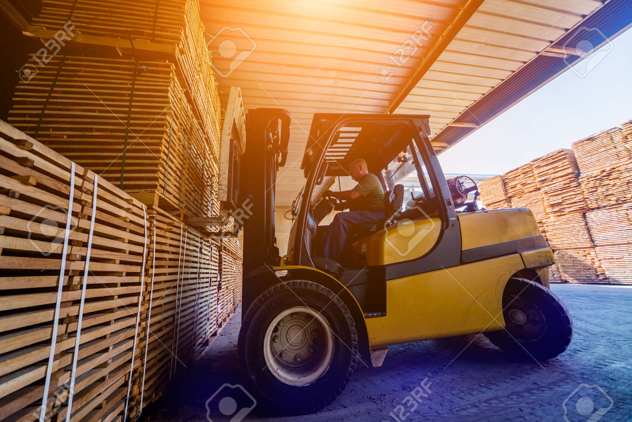 Forklift loader load lumber into a dry kiln. Wood drying in containers. - 140503921