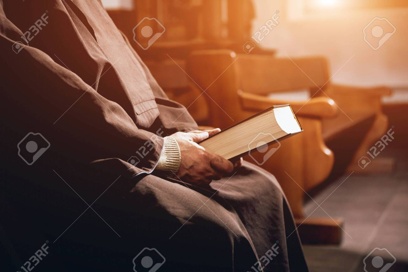 A monk in robes with holy bible in their hands praying in the church - 141188511