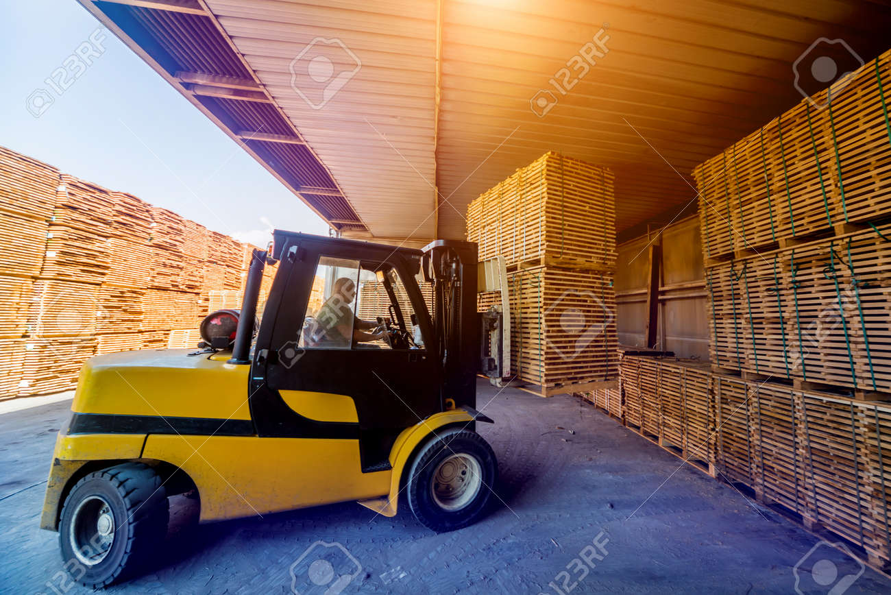 Forklift loader load lumber into a dry kiln. Wood drying in containers. Industrial concept - 142966002