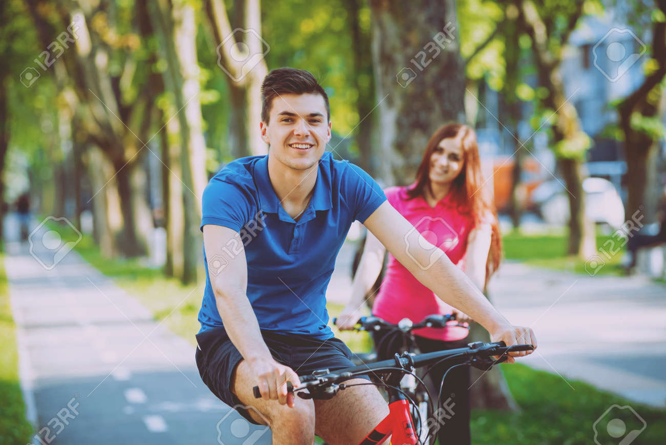 Cycling young couple. In the park. Beautiful bicycle lane. - 146771368