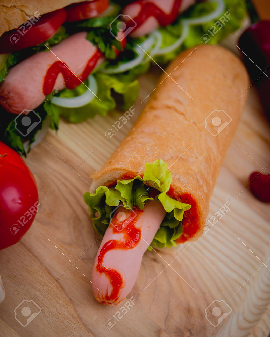 Large hot dog with vegetables on the table. Kitchen - 147639414