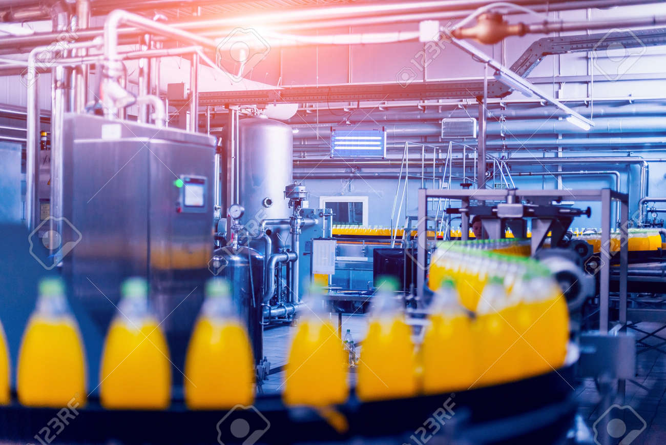 Beverage factory interior. Conveyor with bottles for juice or water. Modern equipments - 148720890