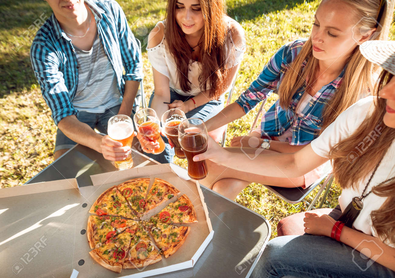 Cheerful friends on picnic in the park. Eating pizza - 150988961