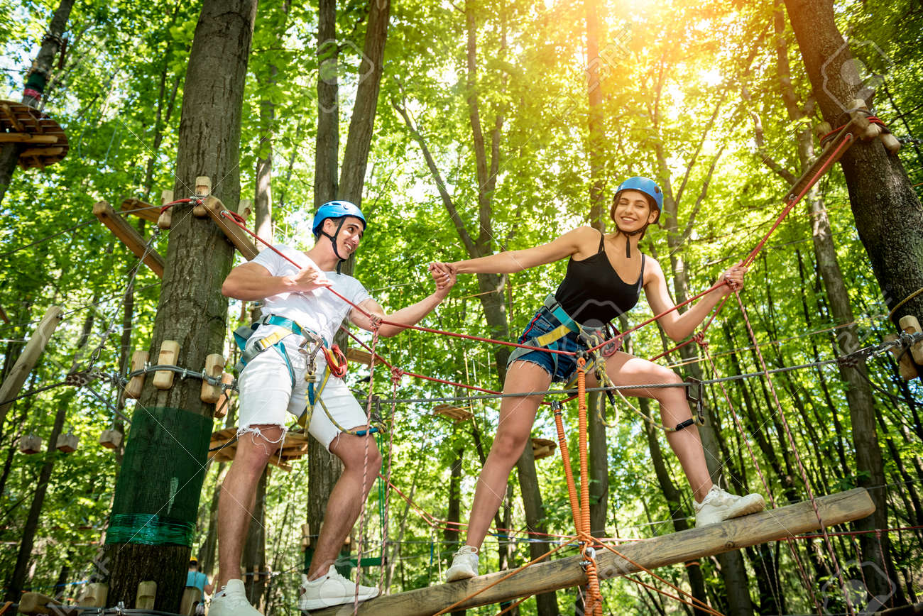 Young couple having fun time in adventure rope park. - 155595312