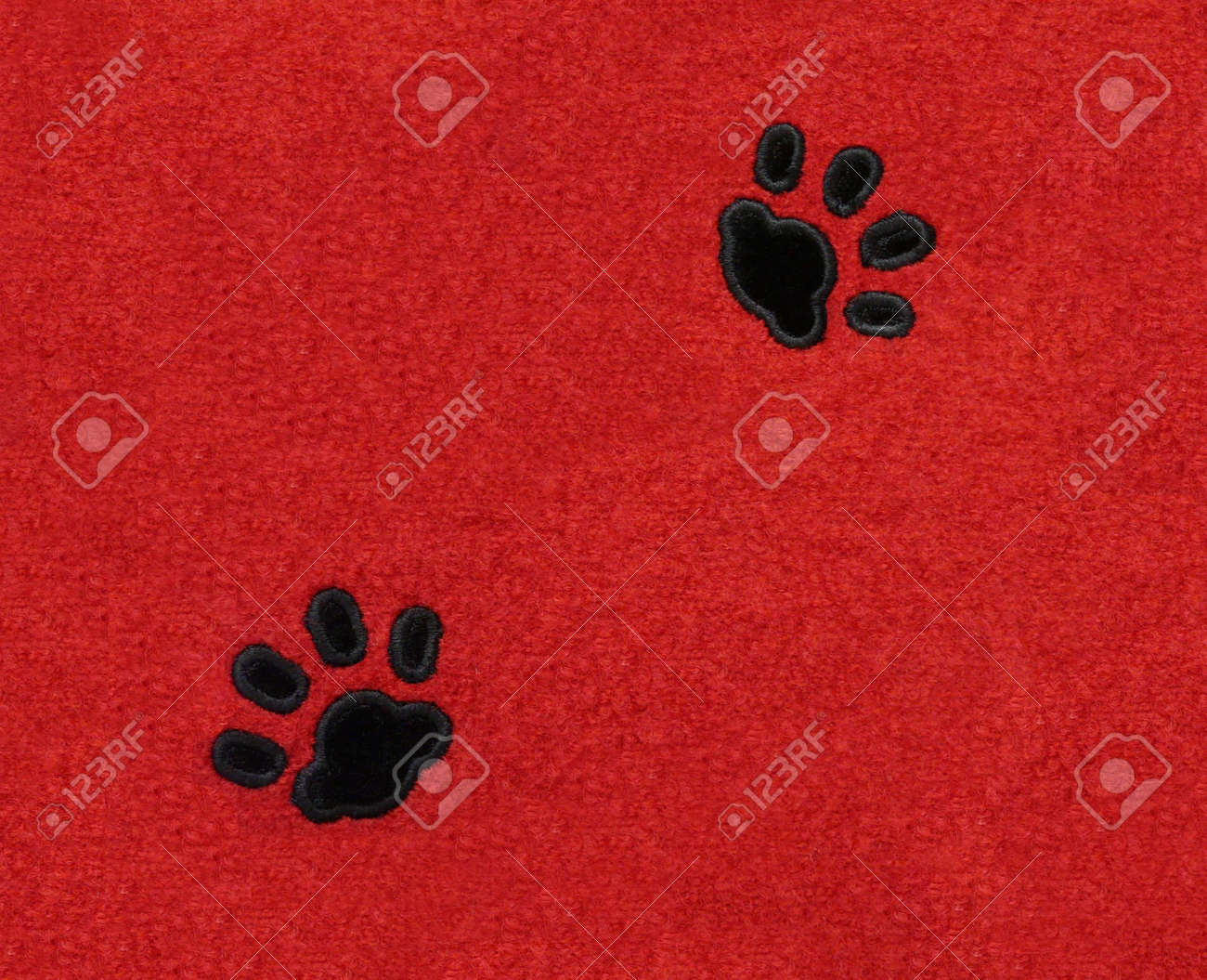 Two black velvet pawprints of a cat on red rectangular fabric. Stock Photo - 7093031