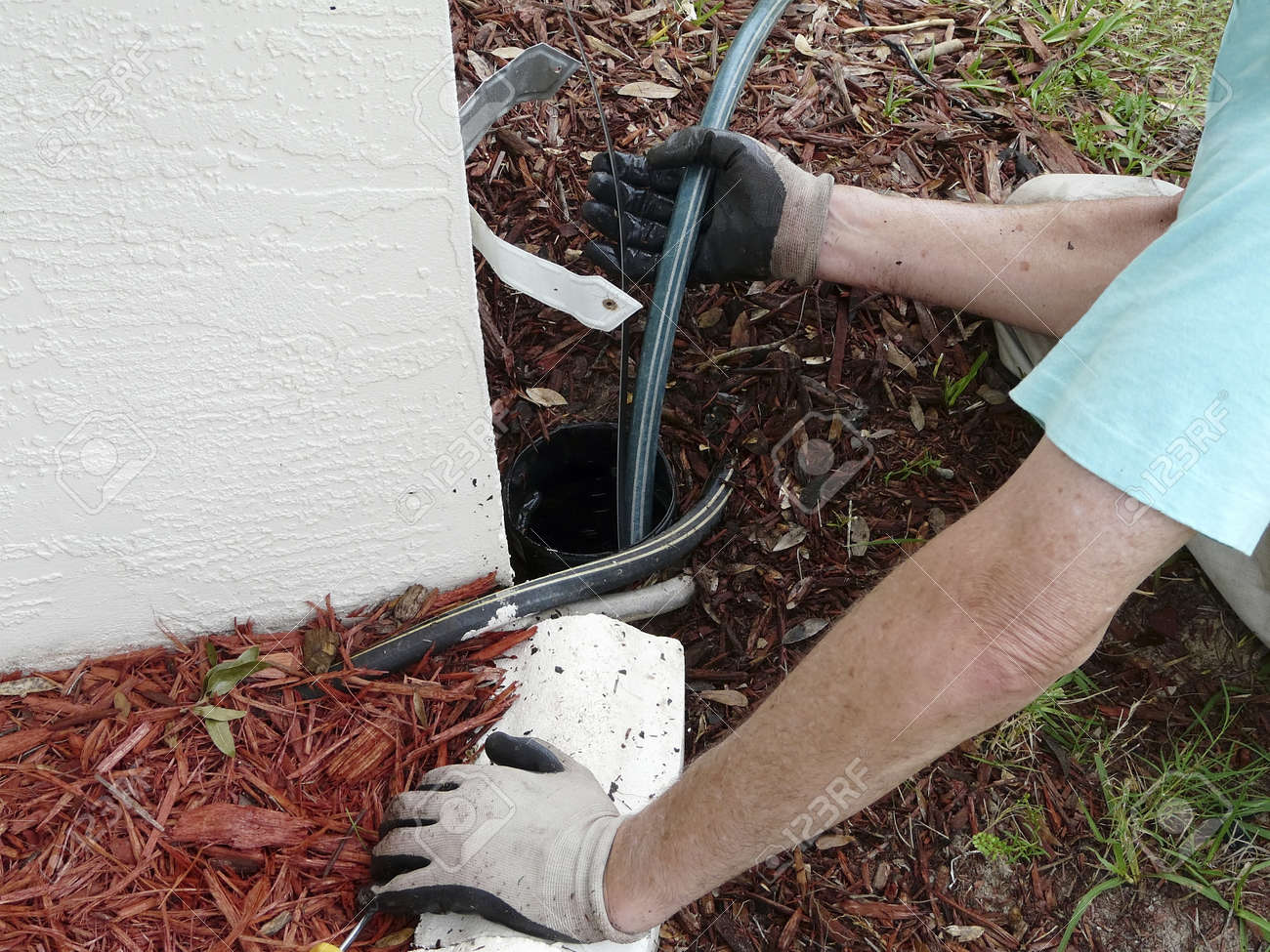 Homeowner uses sewer snake or rod to clear a blockage of dirt and leaves in the & Homeowner Uses Sewer Snake Or Rod To Clear A Blockage Of Dirt ...
