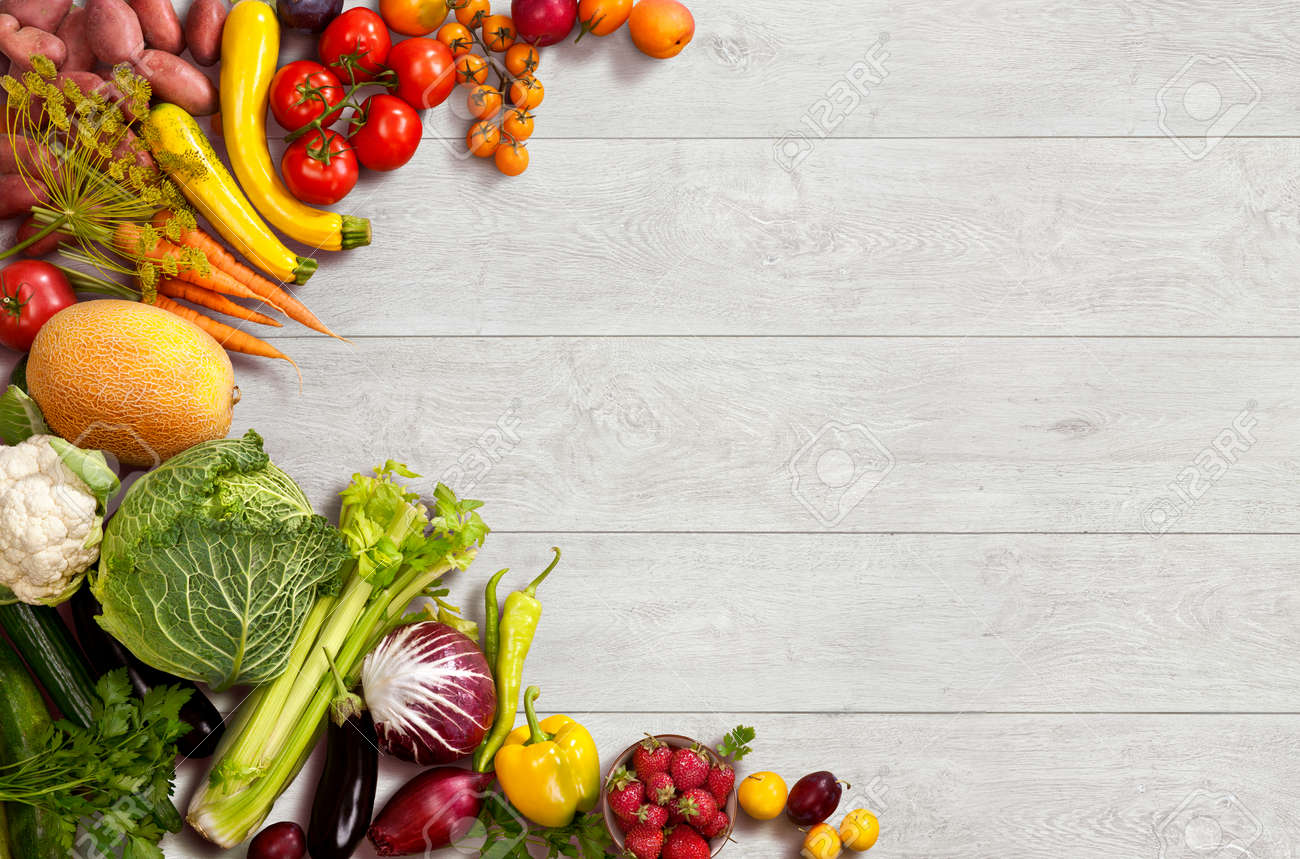 studio photo of different fruits and vegetables on wooden table