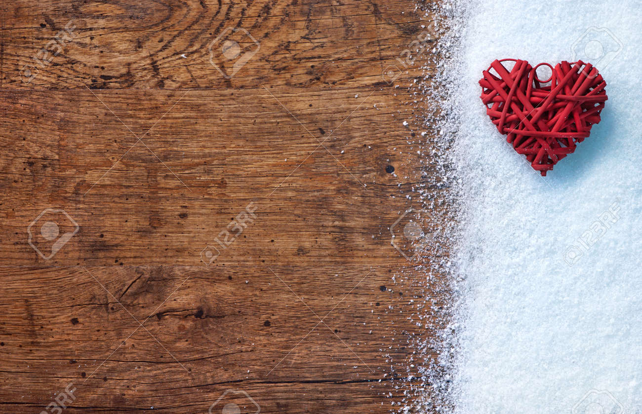 Close Up Red Heart On White Snow Winter And Rustic Background Stock Photo