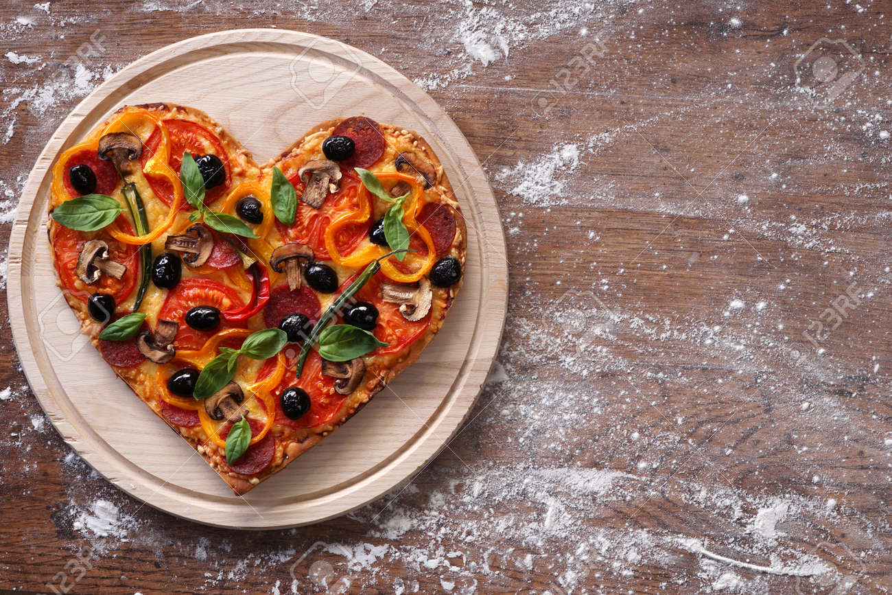 Baked heart-shaped homemade pizza on a cutting board on rustic table, close-up. - 51686562
