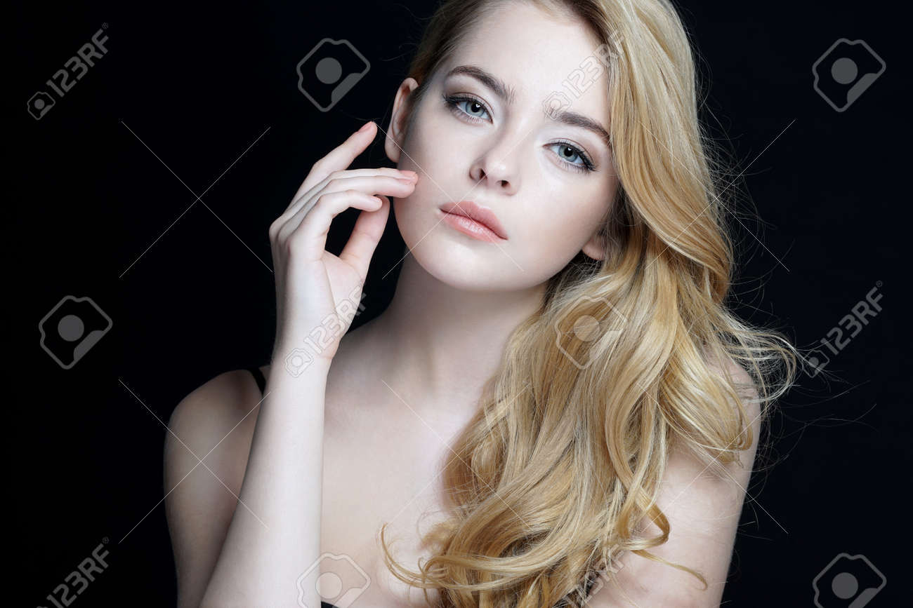 Beautiful young lady with make up face. Close-up of an attractive girl of European appearance on dark background. - 52582632