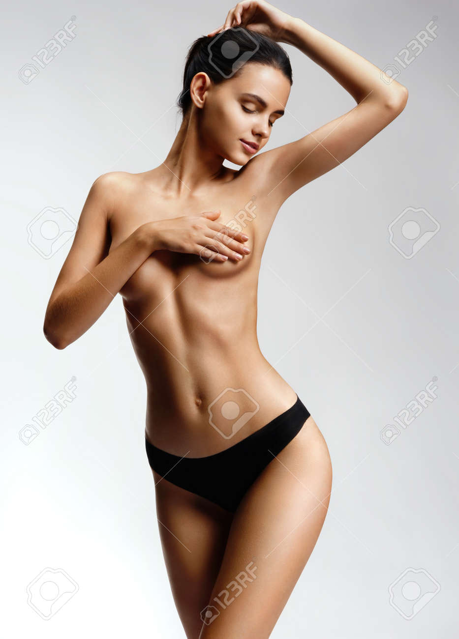 smiling model cover her nude breast. young girl with perfect.. stock