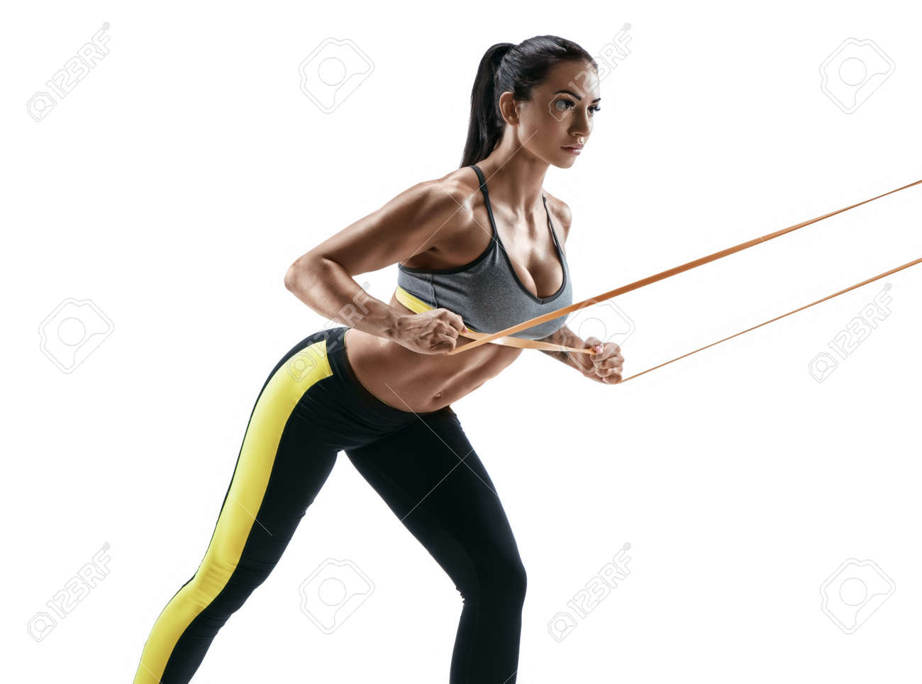 Beautiful athletic woman during workout with suspension straps. Young woman performs fitness exercises on white background. Strength and motivation - 76975242