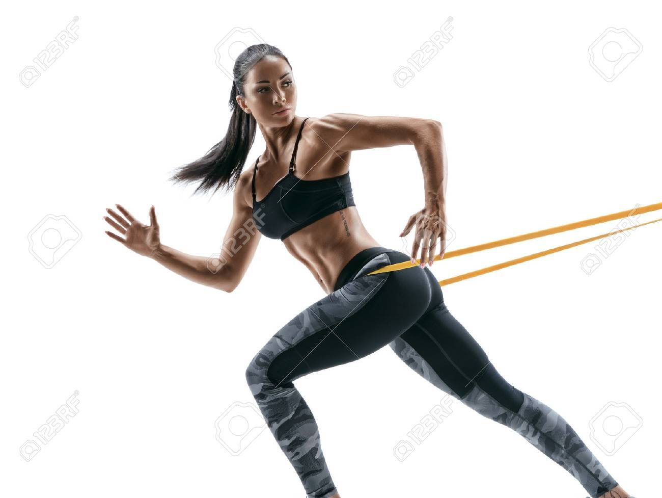 Strong woman using a resistance band in her exercise routine. Young woman performs fitness exercises on white background. - 76708191