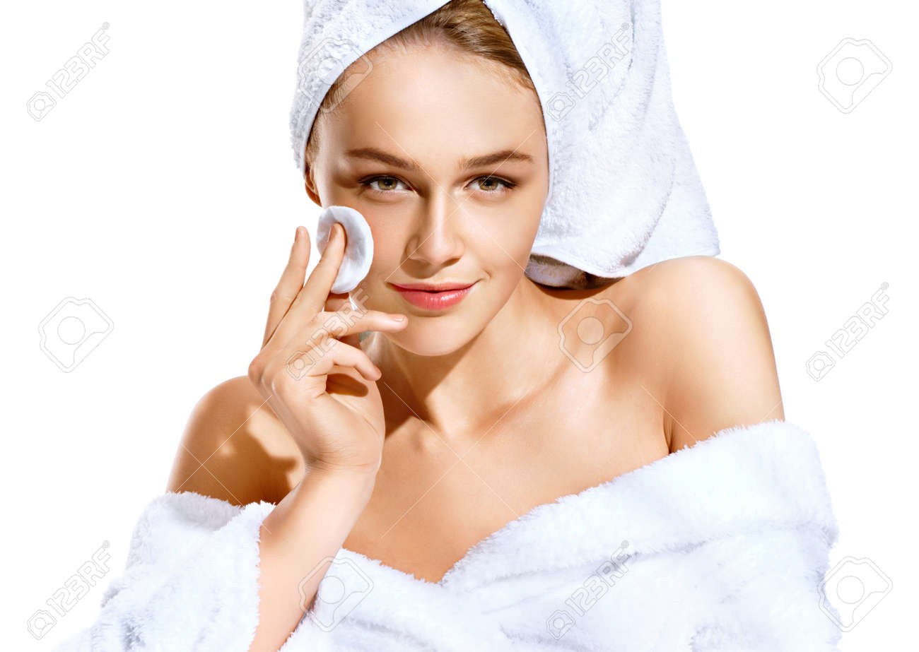 Beautiful sensual girl cleaning her face with cotton swab pad. Photo of girl  after bath