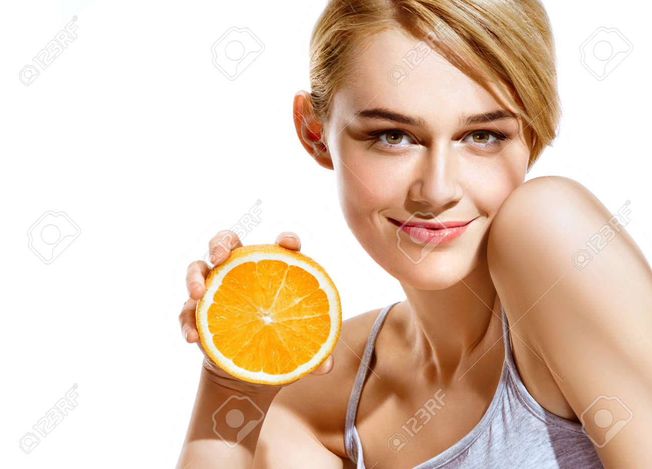 Smiling young girl holding oranges halves on white background. Great food for healthy lifestyle - 76975313