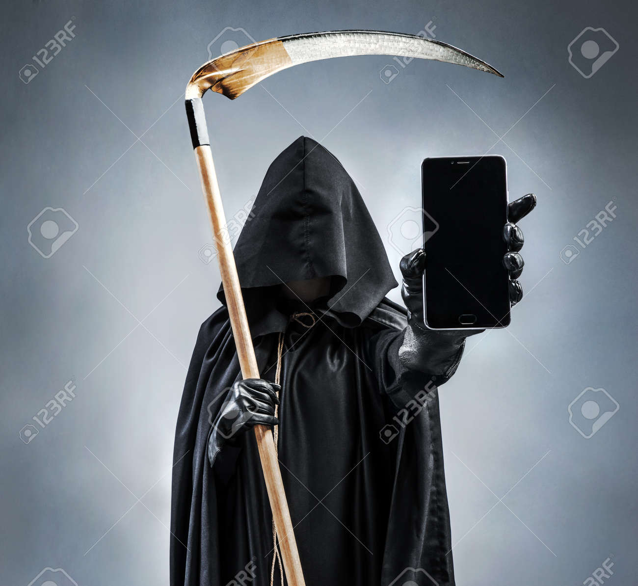 Image of Grim Reaper holding and showing black mobile phone with blank black screen. Photo of silhouette grim reaper with smartphone. Death - 78509180