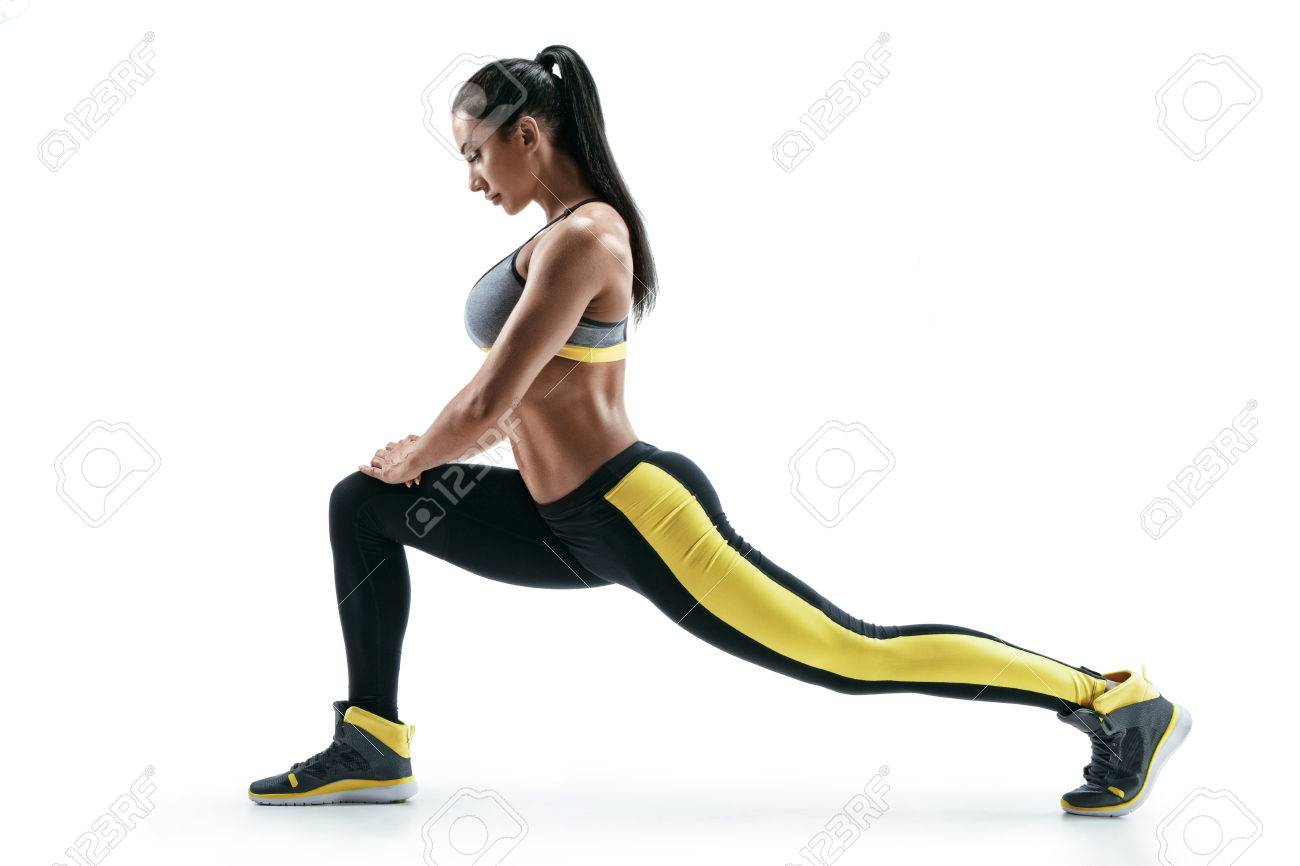 Fitness woman doing stretching workout. Full length shot of young woman on white background. Stretching and motivation - 78518366