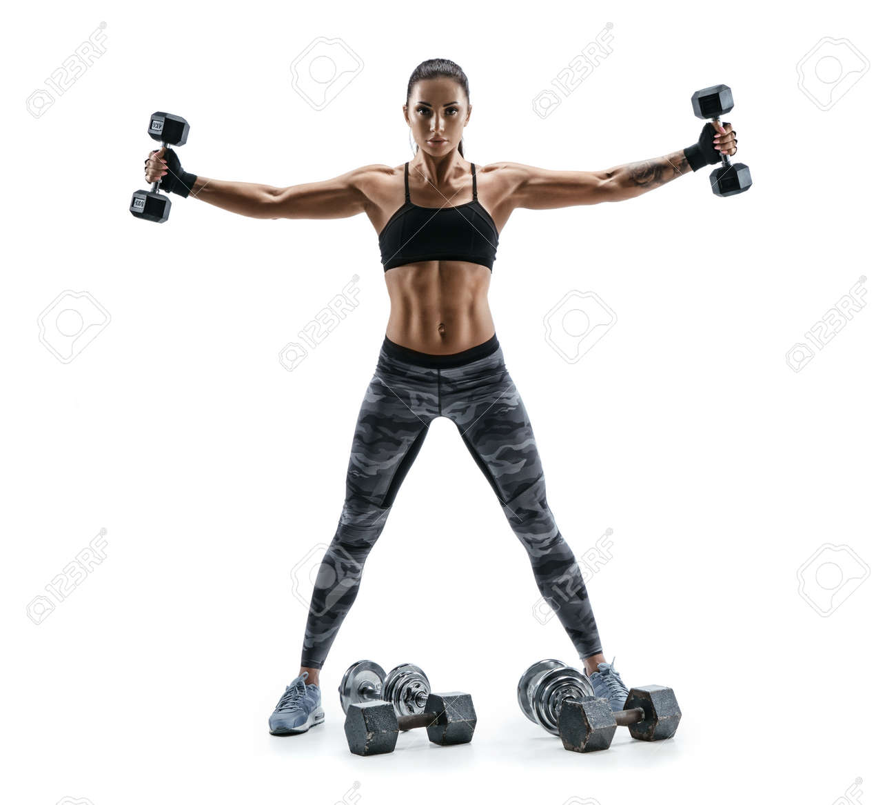 Fitness model exercising with dumbbells in both hands. Photo of muscular woman isolated on white background. Strength and motivation. - 78518372