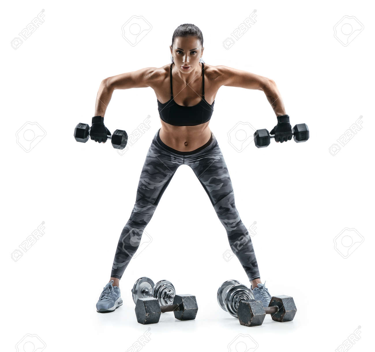 Strong woman exercising with dumbbells for arms. Photo of woman working out with heavy dumbbells on white background. Strength and motivation. - 78518374