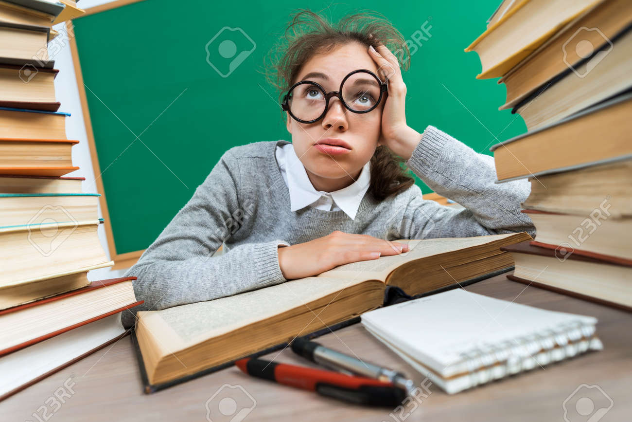 Exhausted or bored young student around a lots of books. Photo of student in classroom, education concept - 82926876