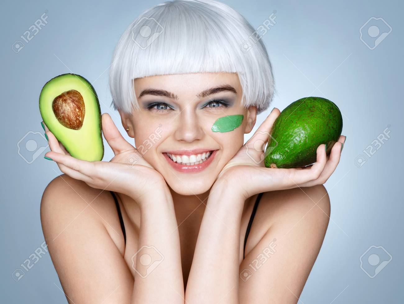 Happy smiling girl with green avocado. Photo of smiling blonde girl on blue background. Skin care and beauty concept. - 88679197