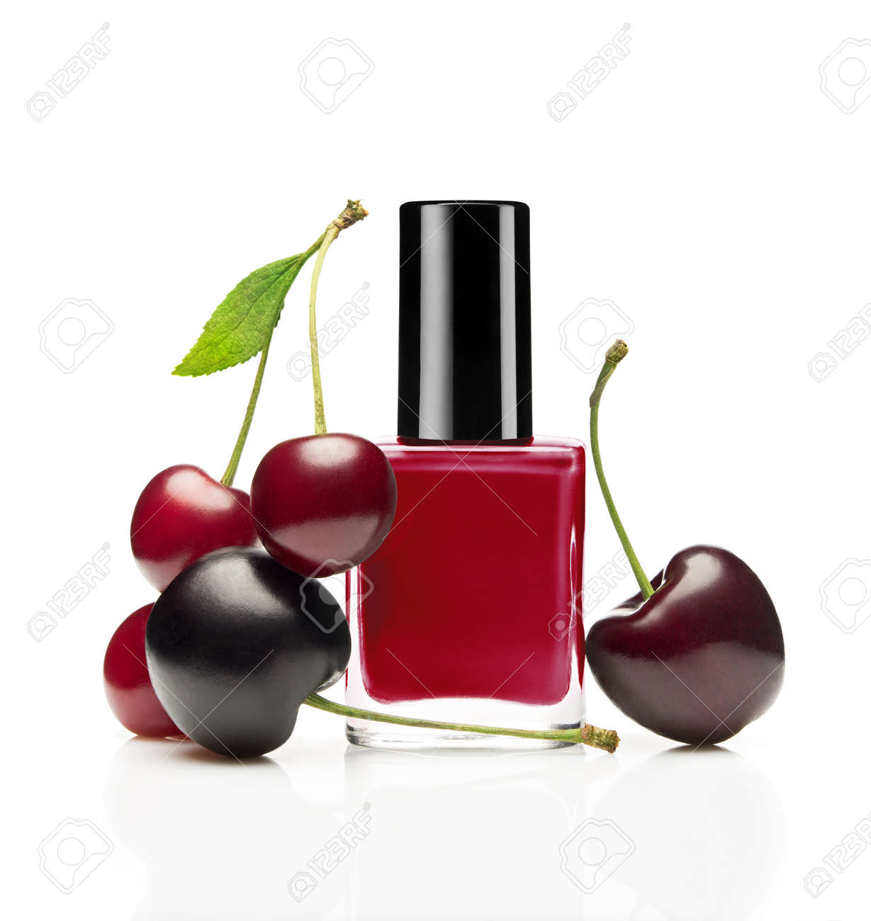 Red nail polish bottle with cherry on white background