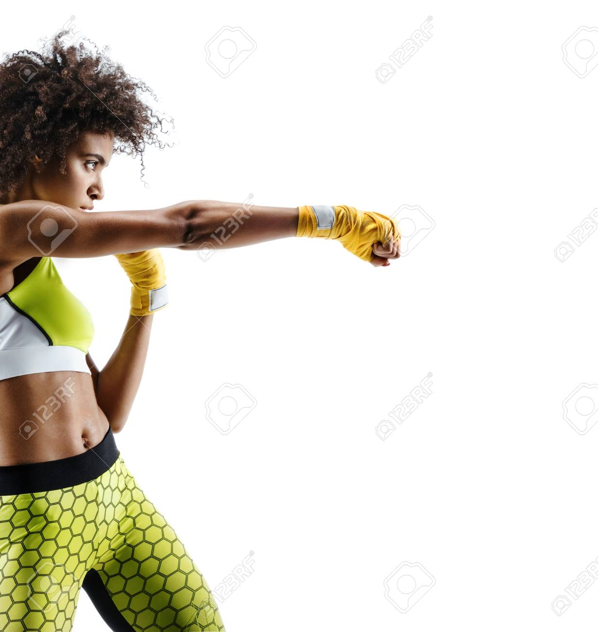 Boxer woman in yellow bandages making direct hit. Photo of sporty african woman during boxing on white background. Dynamic movement. Side view - 91841152