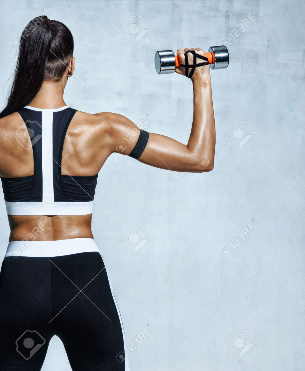 Strong woman working out with dumbbells, flexing her arm. Photo of sporty woman in sportswear on grey background. Rear view - 94700028