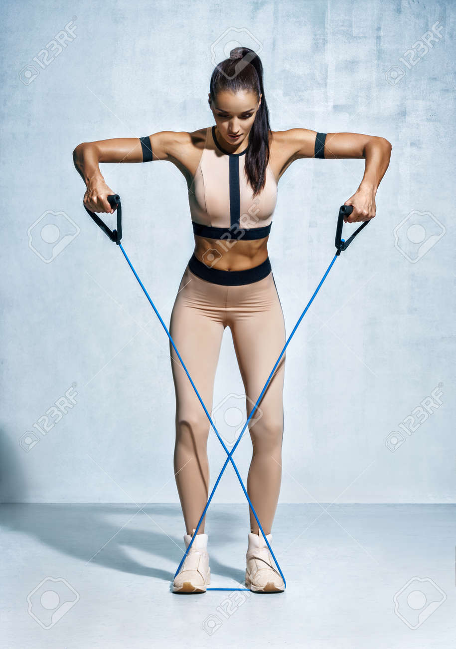 Fitness girl performs exercises with resistance band. Photo of fitness model workout on grey background. Strength and motivation - 94812772