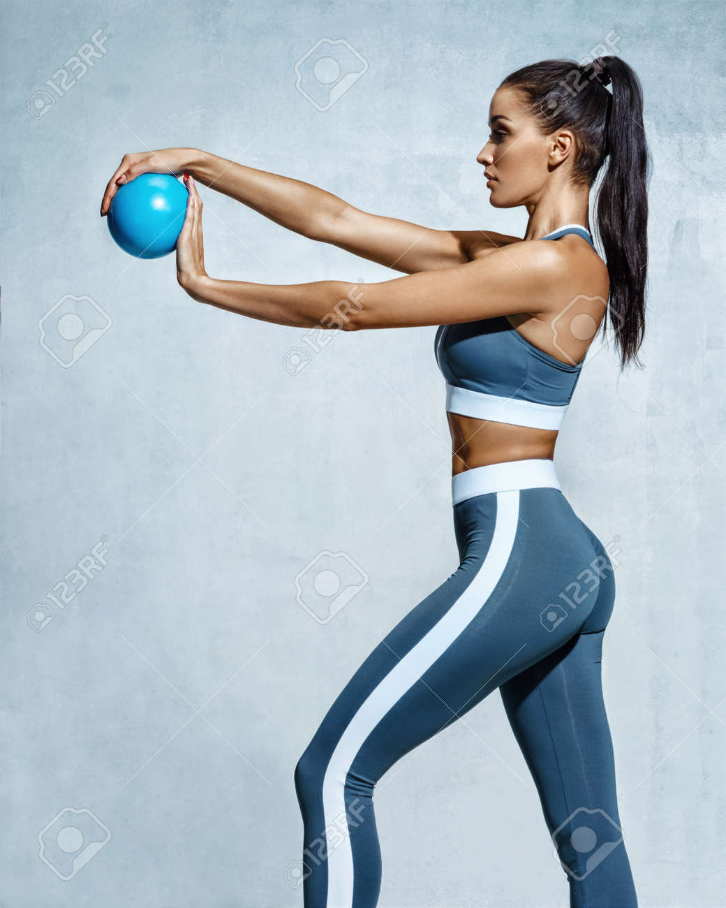 Sporty girl with ball for gymnastics. Photo of strong young girl in training muscles hands on grey background. Strength and motivation - 96881310