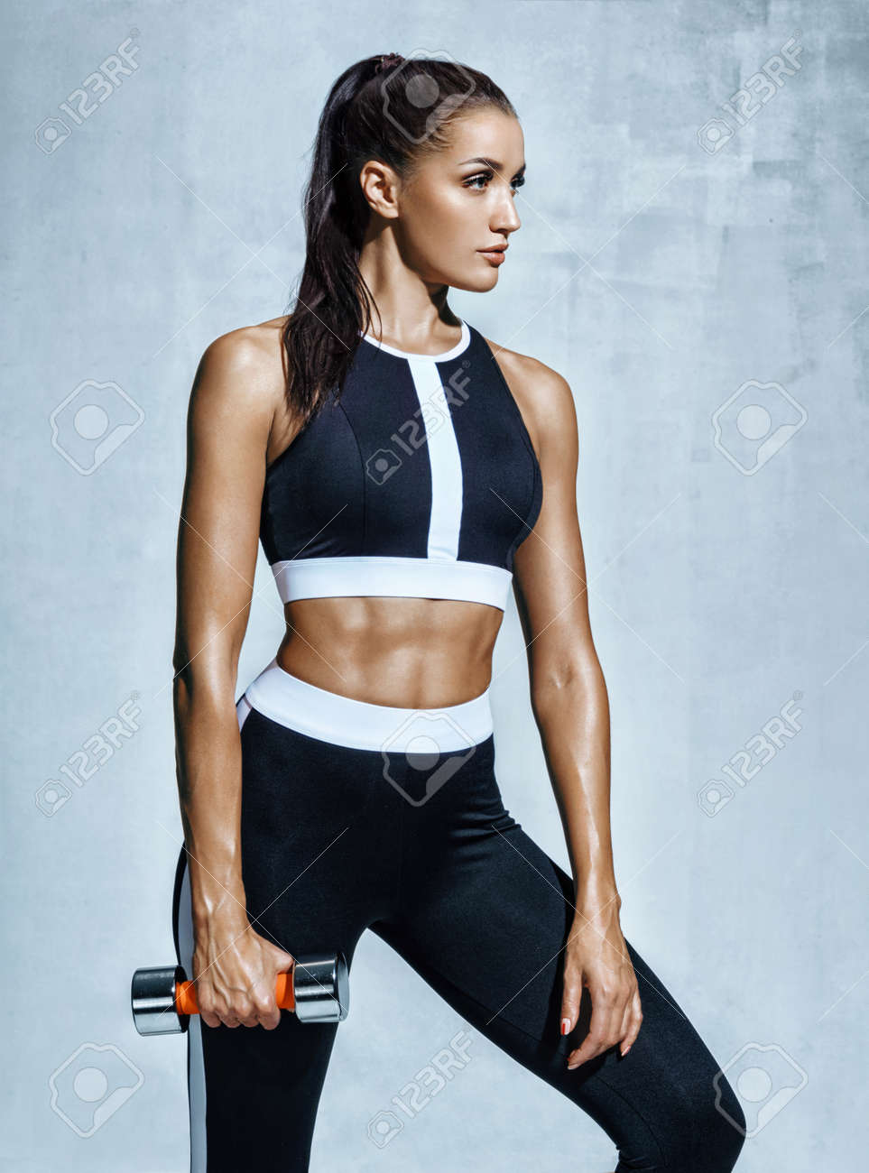 Sporty woman with dumbbell. Photo of muscular woman in black sportswear on grey background. Strength and motivation. - 97763626
