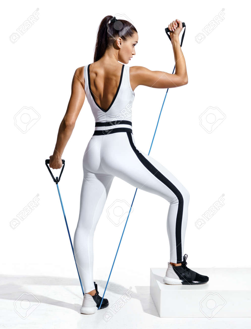 Fitness girl performs exercising with resistance band. Photo of sporty girl in fashionable sportswear isolated on white background. Strength and motivation. Full length - 103368276