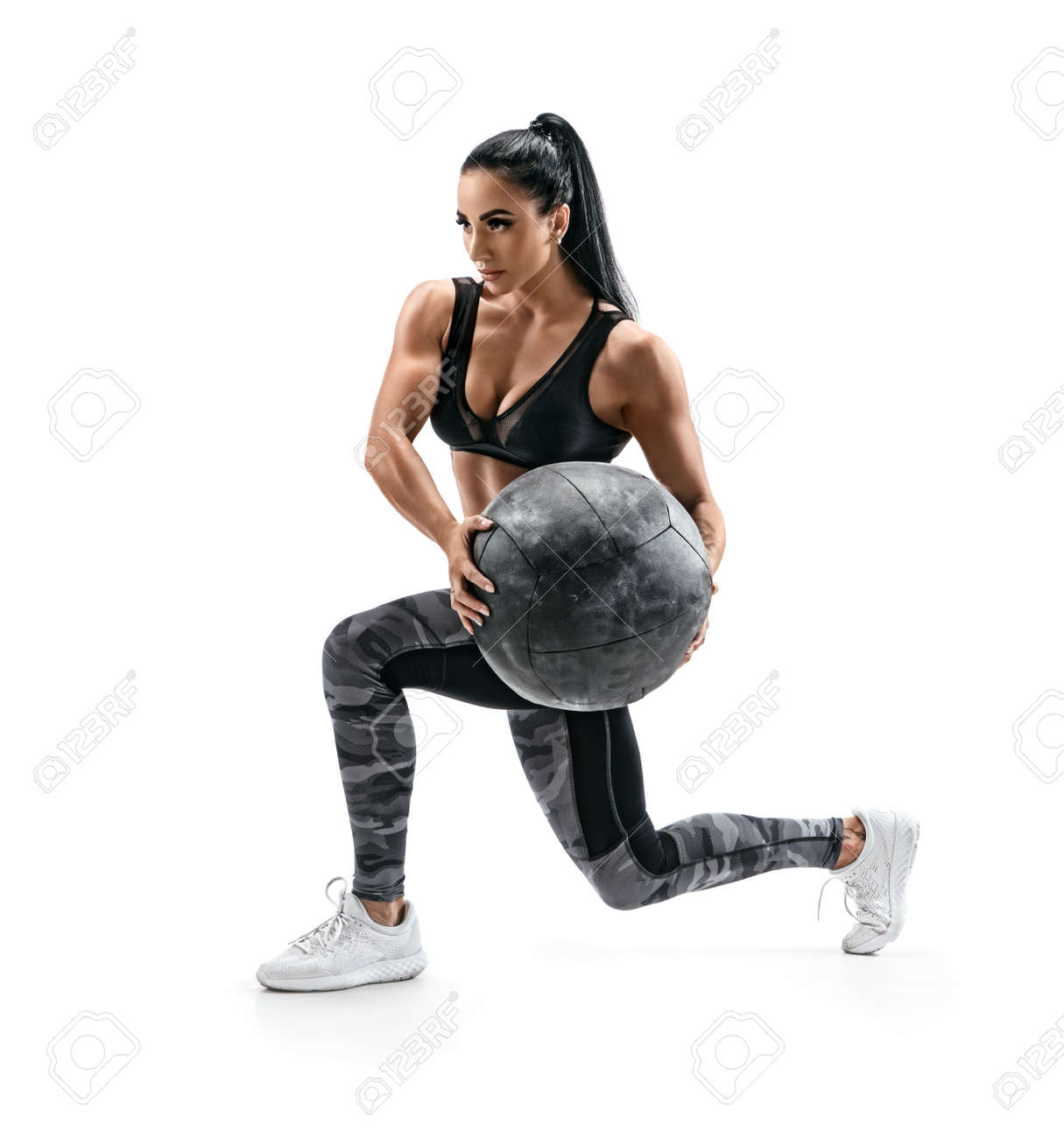 Muscular woman doing lunge twist exercise with med ball. Photo of woman with great physique isolated on white background. Strength and motivation - 105002510